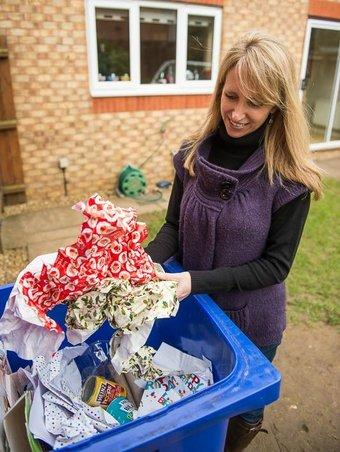 lady putting wrapping apaper into a recycling bin
