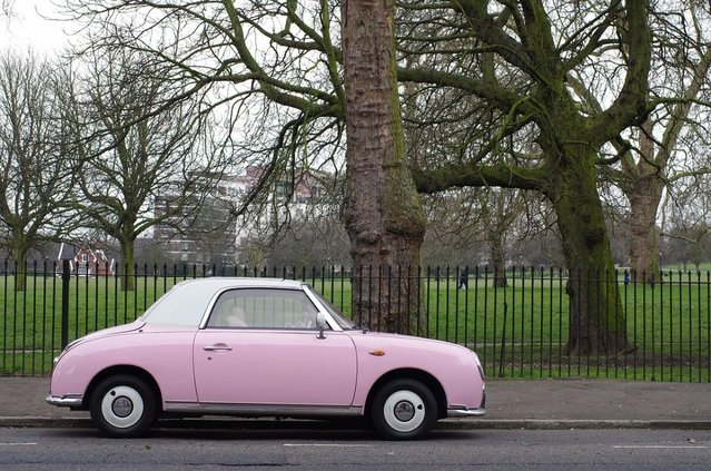pink classic car parked next to a park
