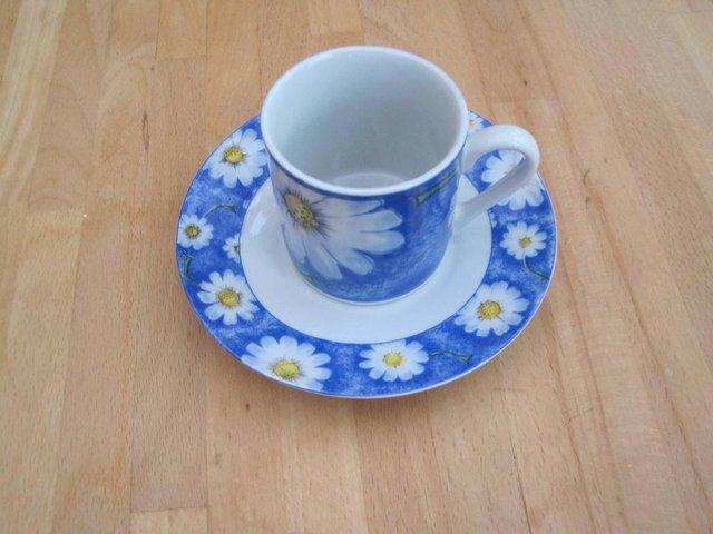 Preview of the first image of White DAISIES on a blue background CUP + SAUCER.