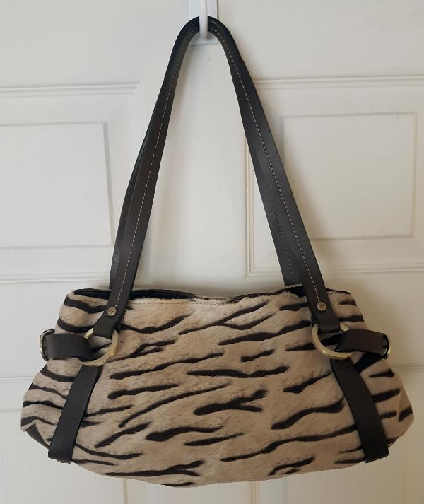 cf3aecda4245 This beautiful genuine designer handbag has a cowhide exterior with a soft  cream lining printed with the words Coty. It has a zipped central  compartment ...
