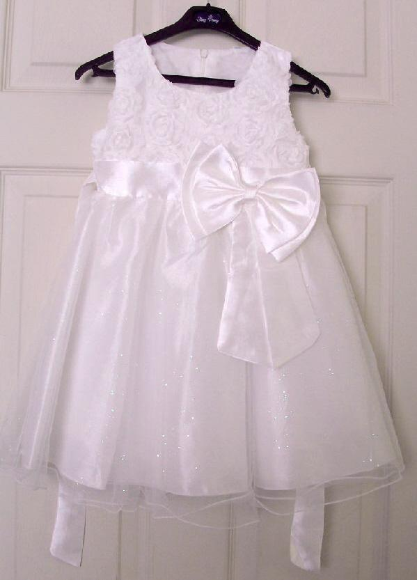 838f4c9665 ... a white flower bodice and satin look skirt with a net overlay. It is  finished off with a pretty satin look waistband and a large bow.