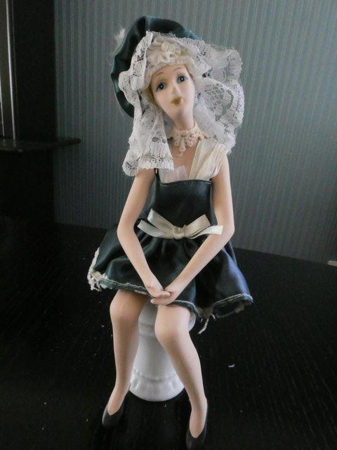 Preview of the first image of Antique articulated china painted doll on pedastal seat.