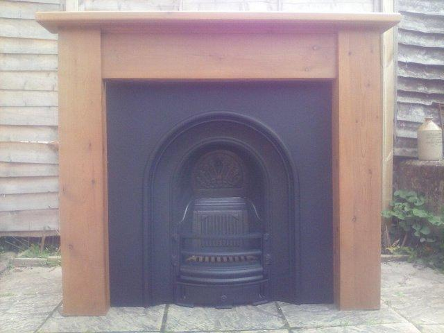 Preview of the first image of LARGE CAST IRON FIREPLACE AND SOLID PINE SURROUND..