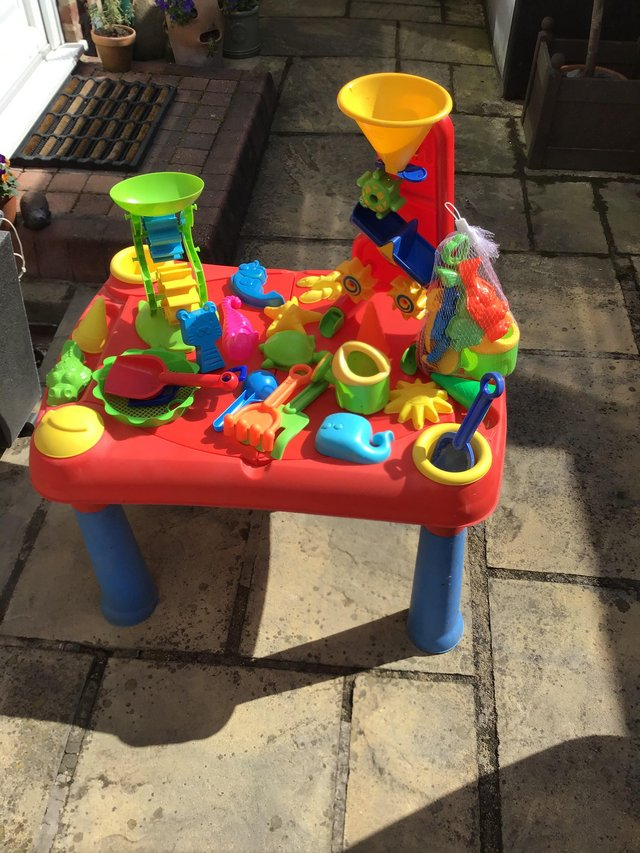 Preview of the first image of Child sand pit/play table with assorted toys.