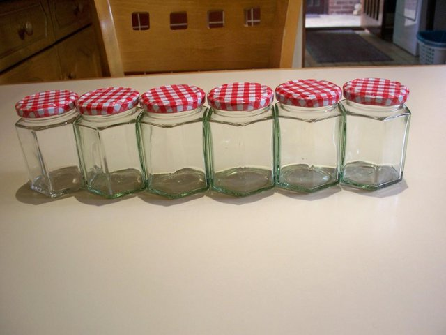 Preview of the first image of 6 used glass jam jars 8oz hexagonal with red gingham lids.