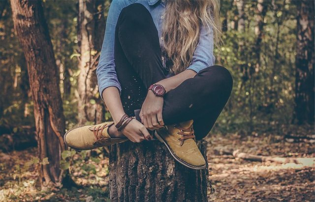 fashion photo of a girl sat in woodland